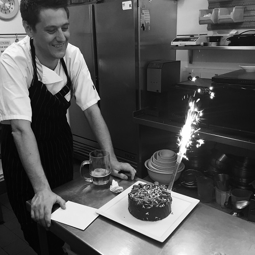 Chef with a birthday cake with a candle in it